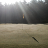 A sunny day view of a hole at Alpine Meadows Golf Course