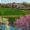 A spring day view of the clubhouse and a green at Kalamazoo Country Club.