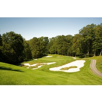 The fourth hole on the Threetops golf course at Treetops Resort features a small green with large bunkers left and right.