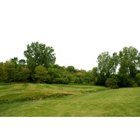 Leslie Park Golf Course's 10th hole is tucked behind a mound and creek.
