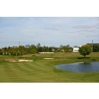 The Orchards Golf Club's 18th hole features an approach shot downhill over a pond.
